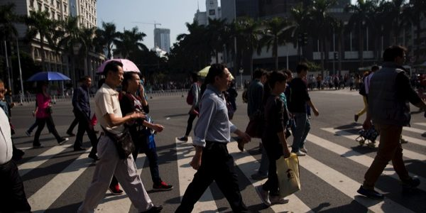 Pedestrians cross a street in the Gongbei district of Zhuhai