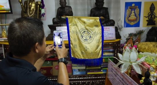A visitor photographs a Leicester City banner at the Wat Traimitr Withayaram temple in Bangkok