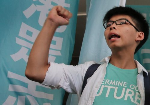 Teen protest leader Joshua Wong shouts slogans outside a magistrate's court in Hong Kong