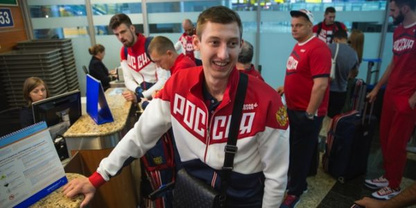 Volleyball player and Russia's National Olympic team member Dmitrij Volkov (center) wait at a check-in desk before his team's departure for Rio Olympics
