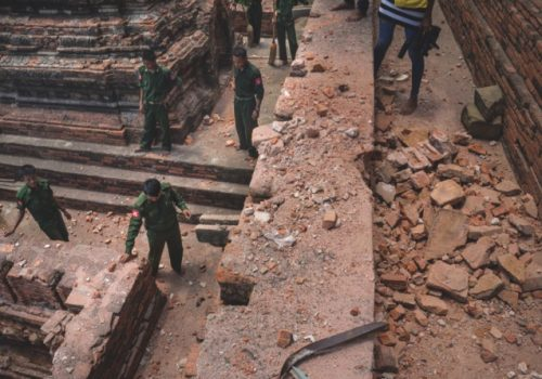Military personnel stand as they clear debris at a temple that was damaged by a strong earthquake in Bagan, yesterday
