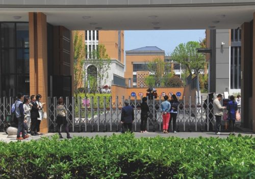 In this undated photo, parents wait for their children at the gate of the new campus of Changzhou Foreign Languages School