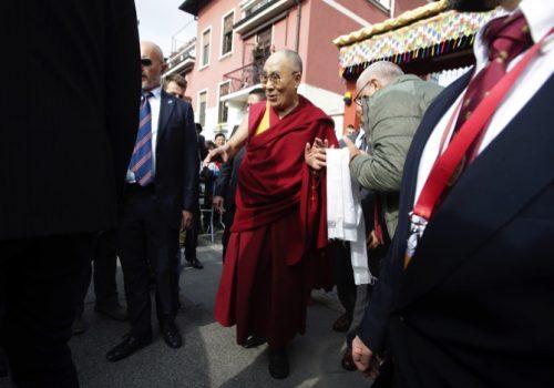 The Dalai Lama Tenzin Gyatso, center, leaves after visiting a Tibetan Buddhist institute, in Mila