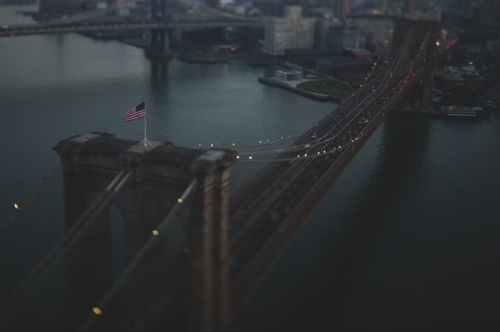 The U.S. flag flies as cars drive over the Brooklyn Bridge to downtown Manhattan in this aerial photograph taken with a tilt-shift lens in New York