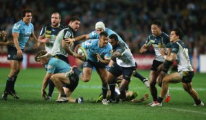 Waratahs' Kurtley Beale, center with ball, breaks away on his way to scoring a try during their Super Rugby semifinal match against the Brumbies