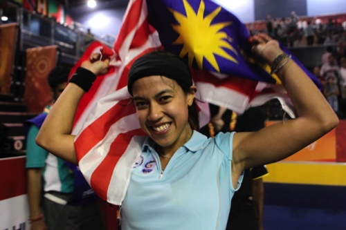 Nicol David celebrates with her national flag after winning the gold medal in the women's singles squash event