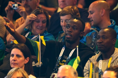 Double Olympic champion Usain Bolt of Jamaica, centre, watches the women's pool A netball match between Jamaica and New Zealand at the Commonwealth Games