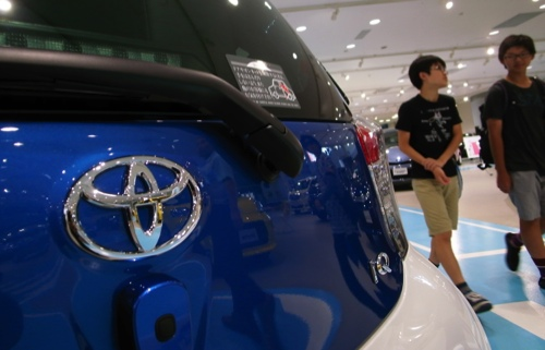 Visitors walk past a Toyota IQ compact car displayed at a Toyota showroom in Tokyo