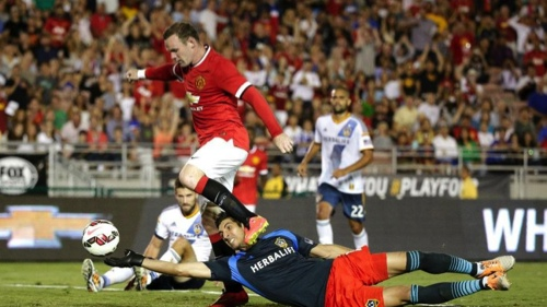 Manchester United's Wayne Rooney, top, scores past Los Angeles Galaxy goalkeeper Jaime Penedo during the first half of a friendly soccer match at Rose Bowl