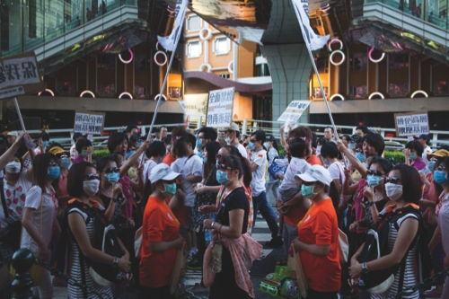 """Gaming workers, reflected in a mirror, protest. Saturday's event is being organized by an online group called """"Guarding Macau People,"""" with strong links to the promoters of the recent casino workers rallies"""