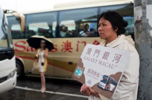 An employee holds a sign for the Galaxy Macau casino resort