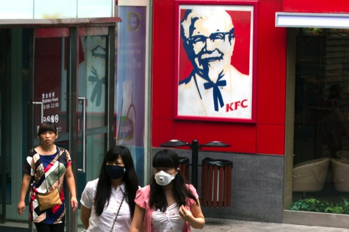 Women wearing masks during a polluted day walk outside a KFC restaurant in Beijing, China