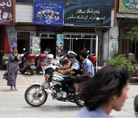 Police officers ride a motorcycle on the streets of Aksu in western China's Xinjiang province