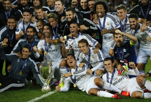 Real Madrid players pose with the trophy after winning the UEFA Super Cup soccer match against Sevilla