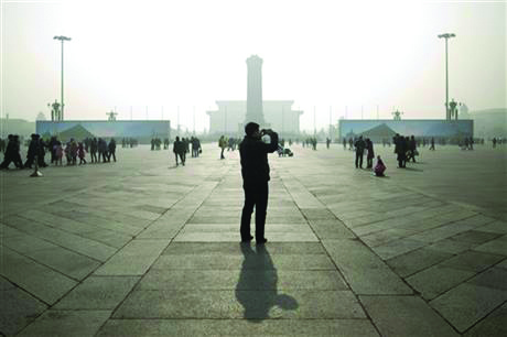 A tourist takes photos during a heavily polluted day in Tiananmen Square in Beijing, China