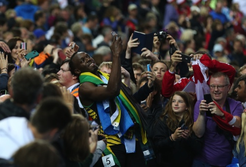 Usain Bolt of Jamaica takes a photo on a smart phone with a member of the crowd as he walks round Hampden Park Stadium after he competed in the men's 4x100 meter relay race