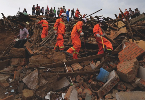 Rescuers and a villager walk past rubble from destroyed houses following a massive earthquake in the town of Longtoushan in Ludian County, Yunnan Province