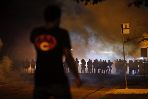A man watches as police walk through a cloud of smoke during a clash with protesters