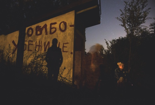 Local residents sit near an entrance to a bomb shelter as they exit to get some fresh air during a short cease fire in Petrovsky district in the city of Donetsk