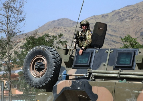 A NATO soldier keeps watch as his vehicle leaves Camp Qargha, west of Kabul, Afghanistan