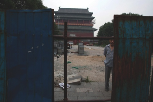 An elderly Chinese resident stands behind barriers around an area undergoing redevelopment in front of the Drum Tower which dates back to 1272 in Beijing, China