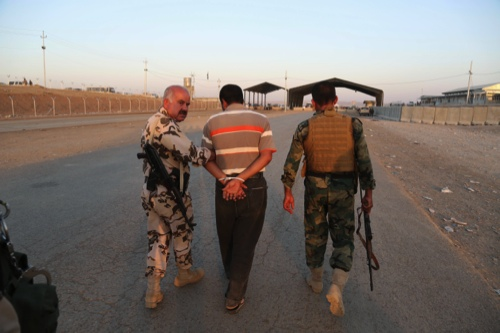 Kurdish Peshmerga fighters detain a man suspected as a militant for the Islamic State group, as airstrikes target Islamic State militants near the Khazer checkpoint outside of the city of Irbil in northern Iraq