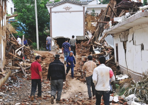 People walk by collapsed houses after Sunday's earthquake in Ludian County of Zhaotong City in southwest China's Yunnan Province