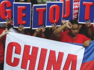 Vietnamese expatriates and Filipinos display placards as they rally in front of the Chinese Consulate in the Philippines