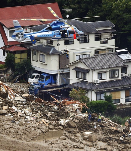 A survivor is lifted by a rescue helicopter from an area devastated by a massive landslide in Hiroshima, western Japan