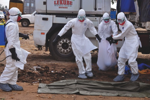Health workers carry the body of a man found in the street, suspected of dying from the ebola virus, in the capital city of Monrovia