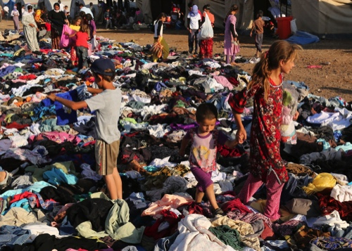 Displaced Iraqis from the Yazidi community look for clothes to wear among items provided by a charity organization at the Nowruz camp