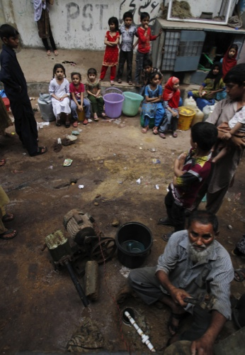 Pakistani children gather by a water distribution point, hoping for the water to come back after being cut, in Karachi, Pakistan