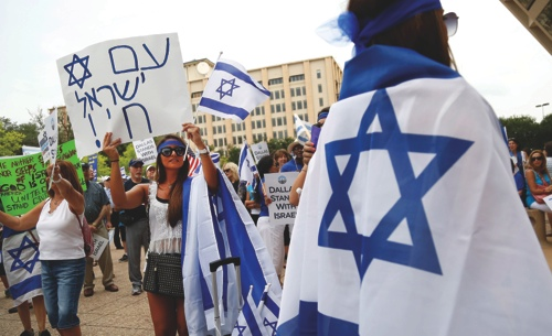 Rebecca Abramov, second from left, holds up a sign in Hebrew during a rally in support of Israel in front of city hall in Dallas, Texas