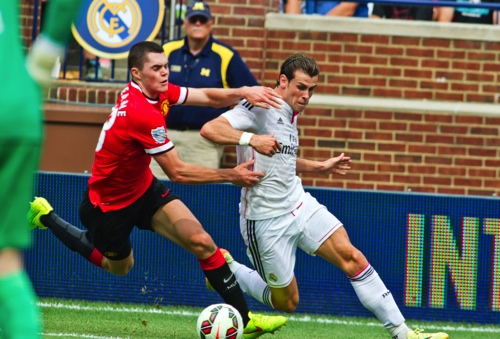 Manchester United defender Michael Keane, left, commits a foul on Real Madrid forward Gareth Bale in the box in the first half of a Guinness International Champions Cup soccer match at Michigan Stadium