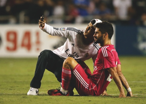 A fan that made it onto the field takes a selfie with Real Madrid's Isco, righ