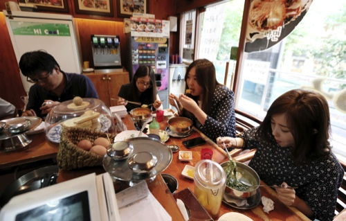 "Customers eat ""ramyeon"" instant noodle at a ramyeon restaurant in Seoul, South Korea"