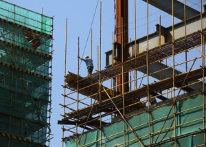 A worker labors on a residential building under construction in Shanghai