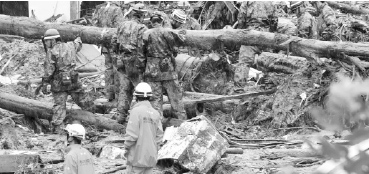 Japan's Self-Defense Force members and fire fighters search for survivors in the rubble