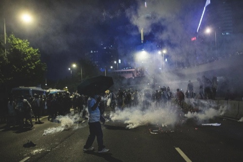 Protestors disperse as tear gas is fired by police during a protest near the central government offices in Hong Kong