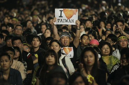 A protester displays a banner supporting Taiwan during a massive protest over the controversial China Taiwan trade pact in front of the Presidential Building in Taipei, Taiwan, Sunday, March 30, 2014