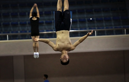 North Korean athletes are seen mid-air as they practice on the trampoline