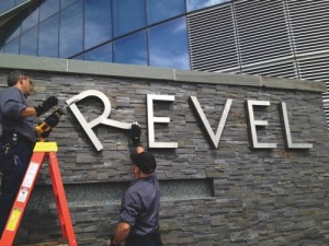 Revel employees Joe Lucchetti,  left, and Robert Fitting remove letters from a sign at Revel hotel-casino