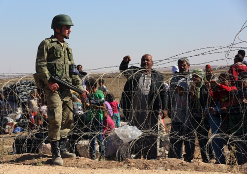 A Turkish soldier stands guard as several hundred Syrian refugees wait to cross the border in Suruc, Turkey