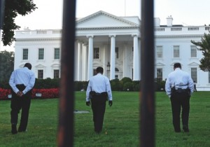 Uniformed Secret Service officers walk along the lawn on the North side of the White House in Washington