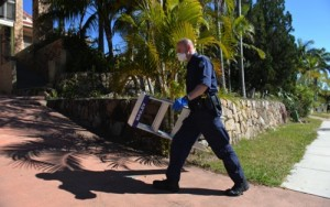 A police officer searches a house in Mount Gravatt, Brisbane, Australia, Thursday, Sept. 18, 2014