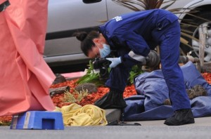 A forensic officer documents objects including a blanket at the scene of a fatal shooting at Endeavour Hills Police Station in Melbourne