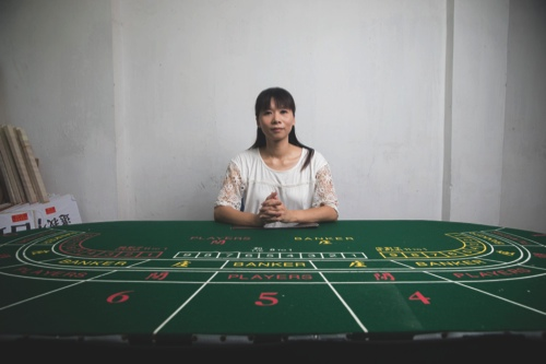 Cloee Chao, co-founder of the Macau Gaming Industry Frontline Workers' Union, poses for a photograph next to a baccarat table at the union office in Macau