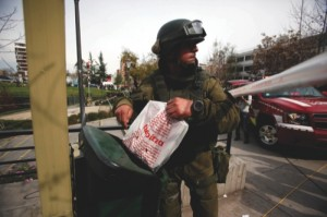 A police explosives expert inspects a garbage container while working near a blast site at a subway station in Santiago