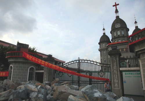 A member of Zengshan Village Christian Church stands near rocks piled up in front of the gate to prevent government workers from moving in equipment to demolish the cross