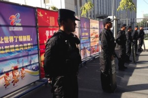Armed policemen stand guard near Xinjiang tourism advertisement boards, which authorities used to block off the road heading to the Urumqi People's Intermediate Court